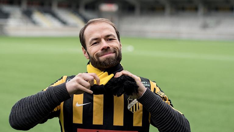 En man med skägg och Häcken-matchtröja knyter en gulsvart halsduk om halsen.