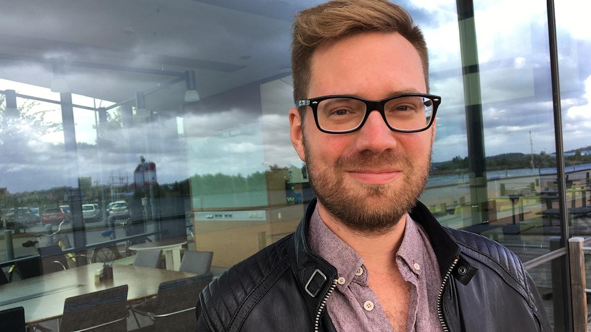 En man med skägg och glasögon.