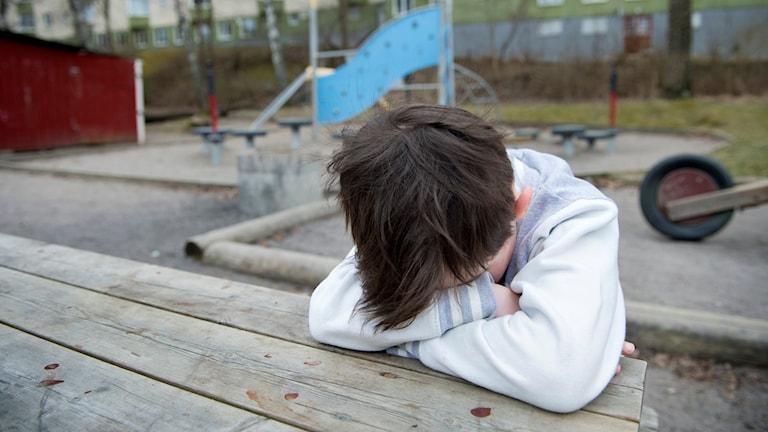 Genre bild på barn som sitter med huvudet nedböjt.