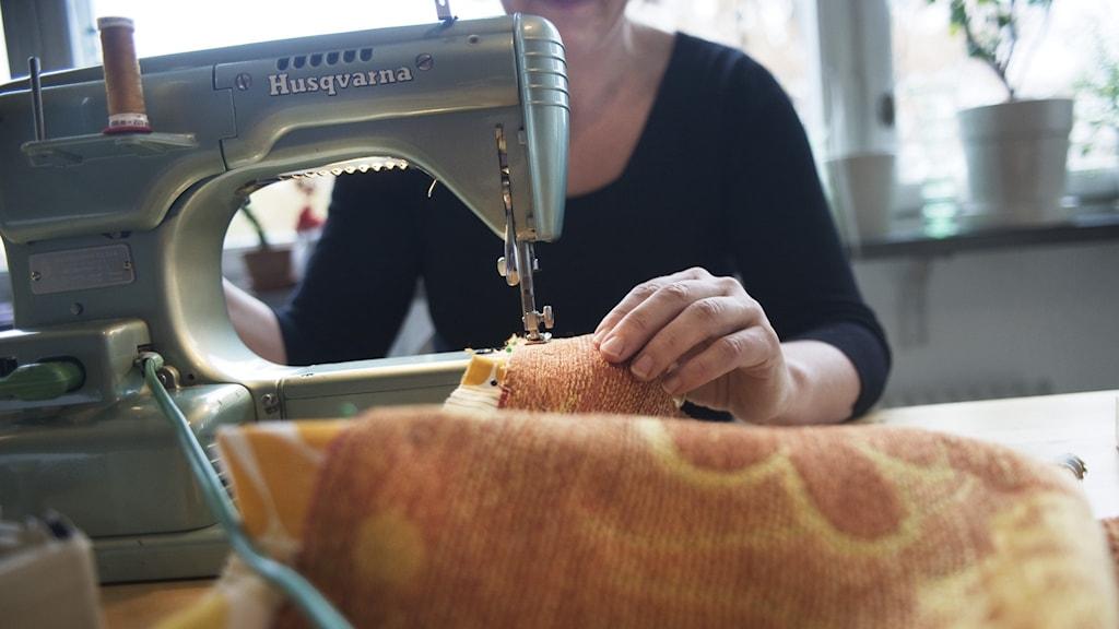 Kvinna som syr på symaskin