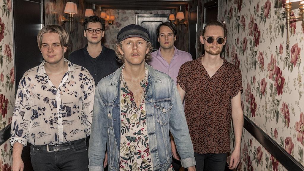 Fem män i färgglada kläder