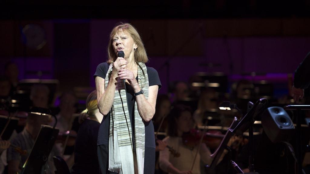 Lill Lindfors sjunger framför mörklagd orkester