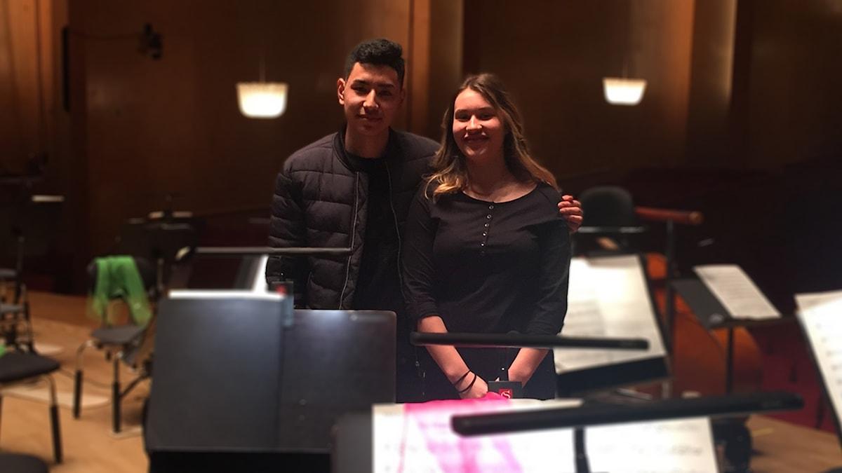 Khalil Alizadeh och Saga Kajanus Nilsson står på scenen bland instrument och notställ.