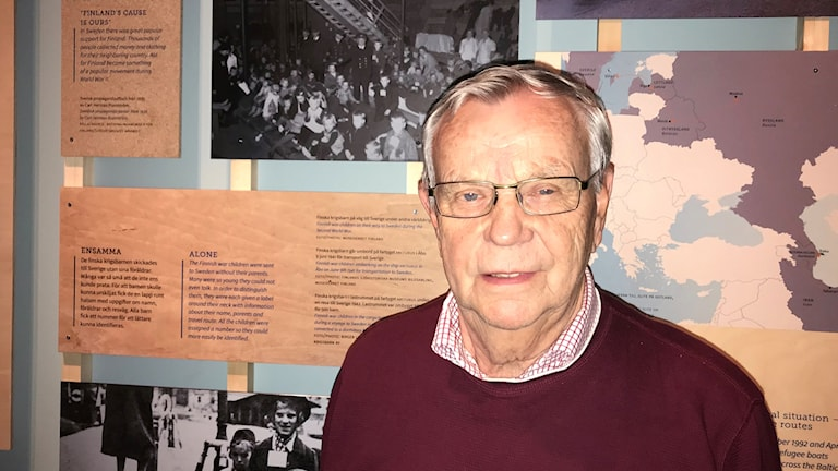 En äldre man med grått hår och glasögon står framför bilder på båtflyktingar och en karta.