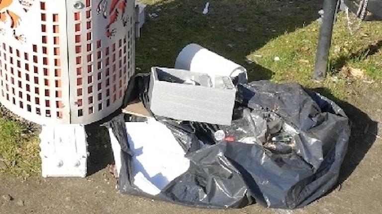 Sopor ligger nedanför en papperskorg på marken