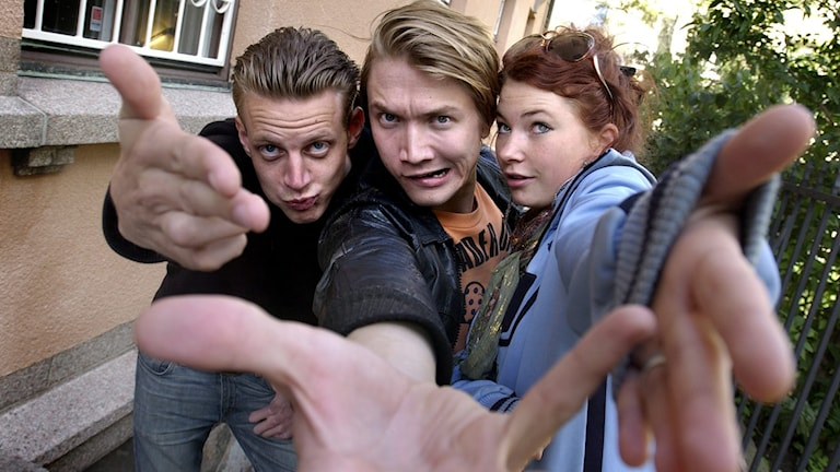 Tre vita personer riktar händerna mot kameran och tittar in.