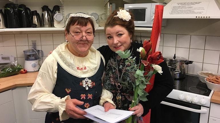 Volontären Bodil Lindqvist i folkdräkt med prästen Marianne Mörk som också klätt sig extra julfin.