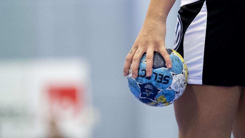 En hand och en handboll.