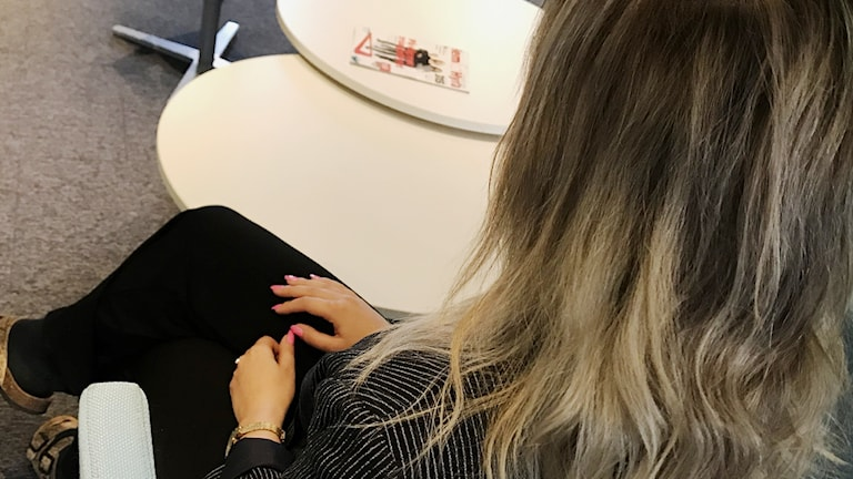 Anonym kvinna sitter med händerna i knät.