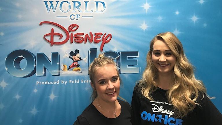 två tjejer framför en backdrop