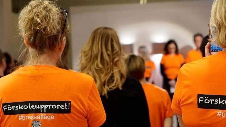 """Kvinnor på möte har orangefärgade t-tröjor på sig med texten: """"Förskoleuppropet""""."""
