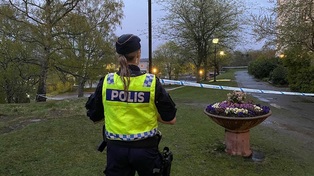 Ryggen på en polis i förgrunden. Bakom henne syns ett blåvitt avspärrningsband.