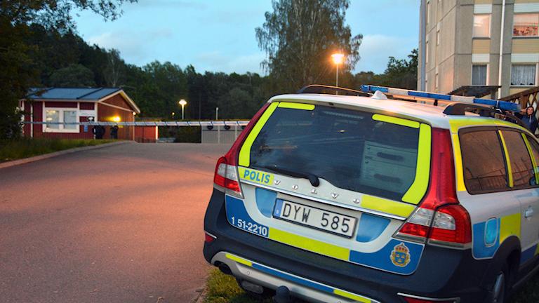 en polisbil i förgrunden. Bakom syns ett litet rött hus bakom polisens avspärrning. Till höger syns ett grått flerfamiljshus.