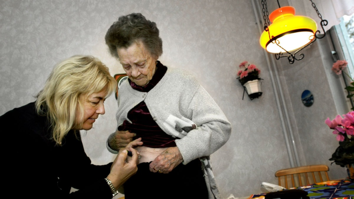 Undersköterska som ger en gammal dam medicin insprutat i magen. Foto: Malin Hoelstad/Scanpix
