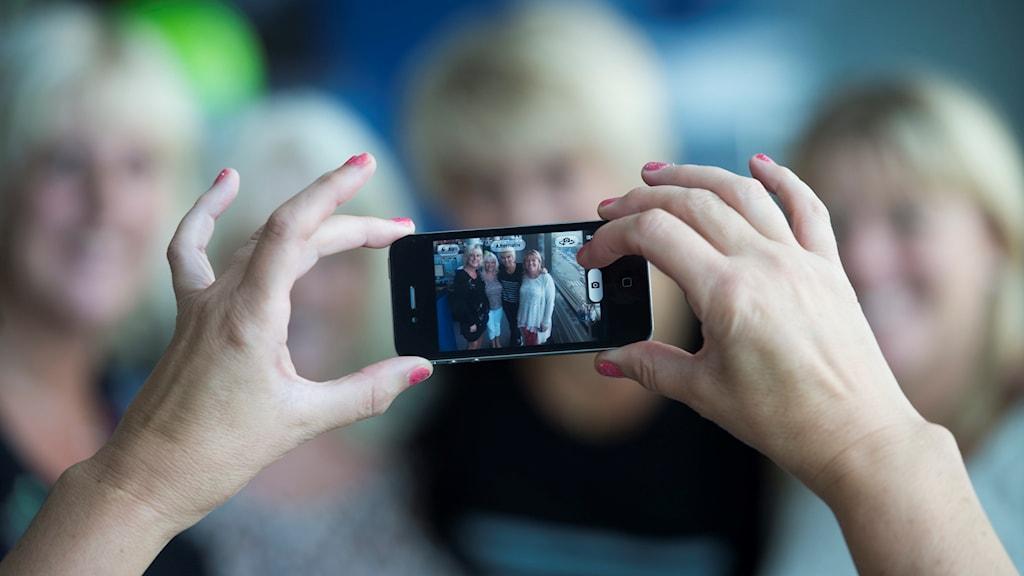 En person fotograferar fyra andra personer med en mobiltelefon.