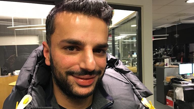 En kille med mörkbrunt hår och skägg och bruna ögon.