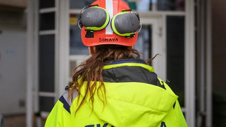 En byggnadsarbetare bakifrån. Hon har reflexgul jacka och orange hjälm på sig. På hjälmen sitter det ett par hörselskydd.