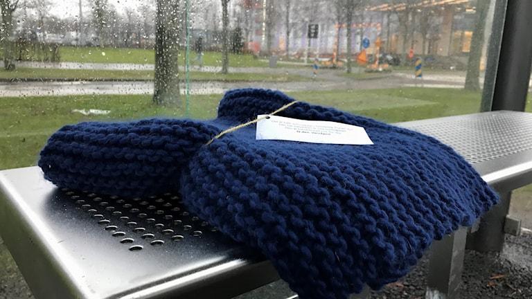 En stickad halsduk av blått garn har lagts som en gåva på bänken i en busskur. På halsduken sitter en papperslapp med text.