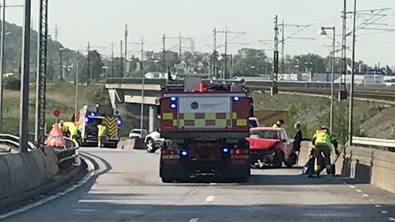 Räddningstjänst vid krockad röd bil.