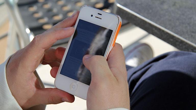 Manshänder håller i en mobiltelefon. Foto: Johanna Storm/SR P4 Göteborg