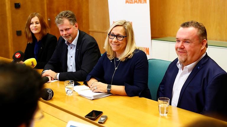 Två män och två kvinnor som sitter vid ett bord