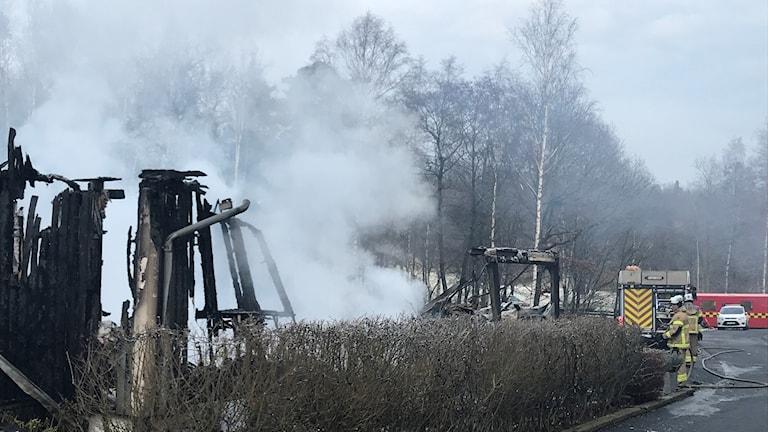 Svarta brända rester av husvägg, rök och en brandman som jobbar vid sidan.