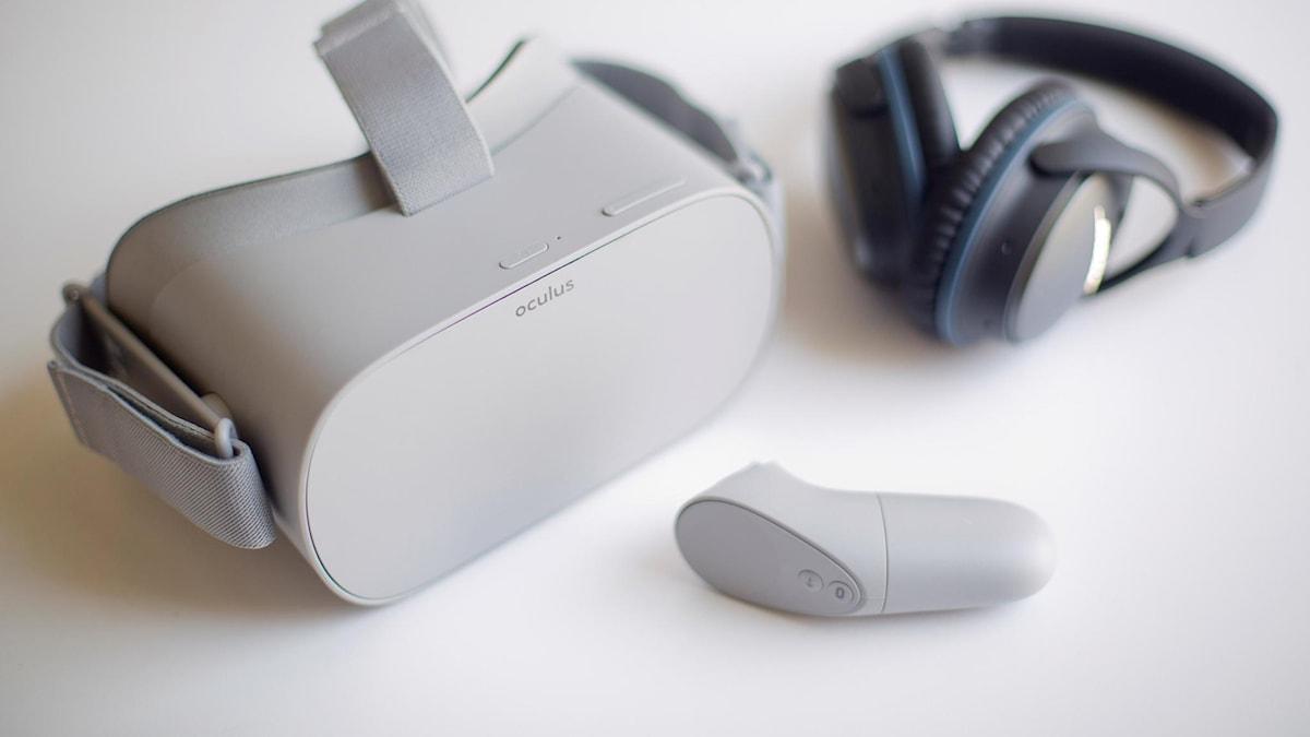 Gråa VR-glasögon, handkontroll och svarta hörlurar på en vit yta