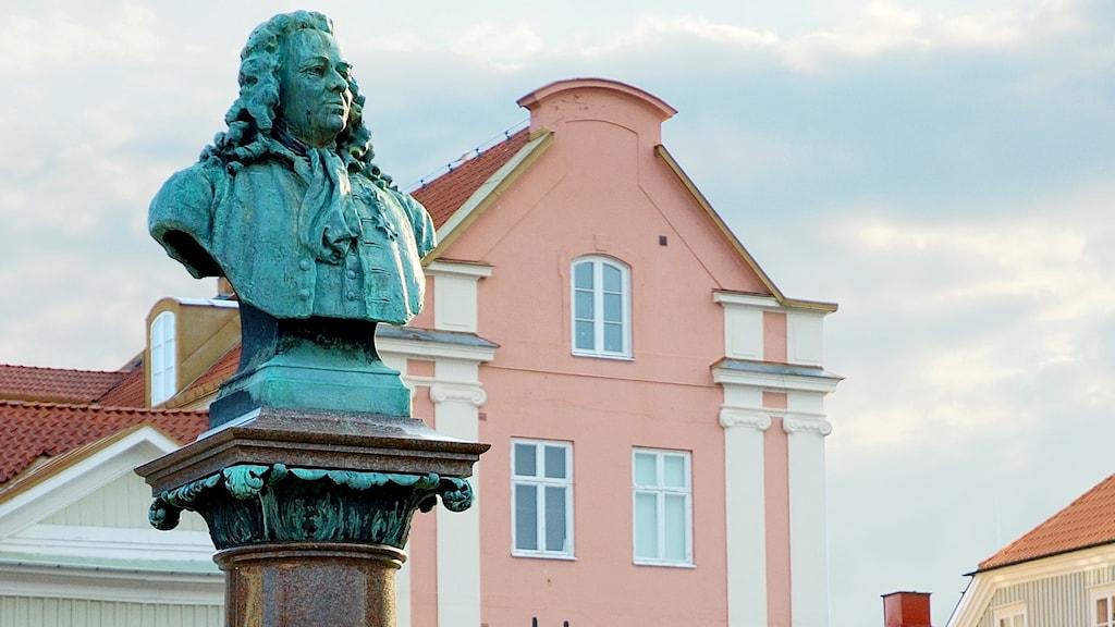 En staty av en man framför en rosafärgad äldre byggnad.