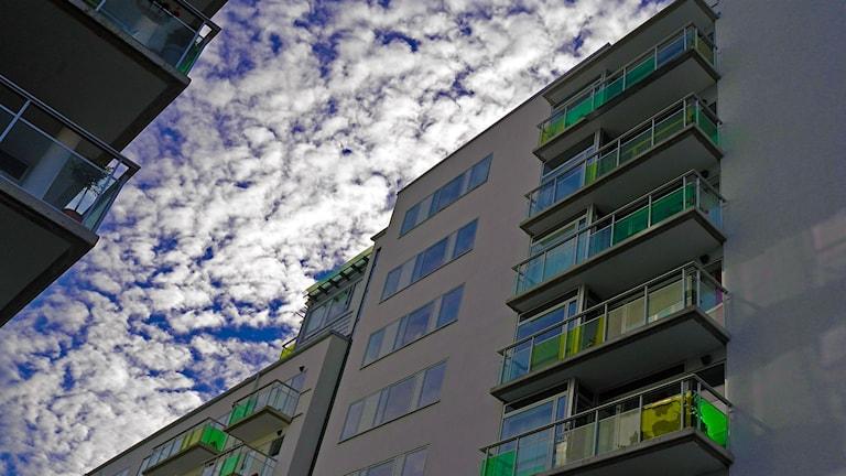 Ett höghus med lägenheter reser sig mot en blå himmel.
