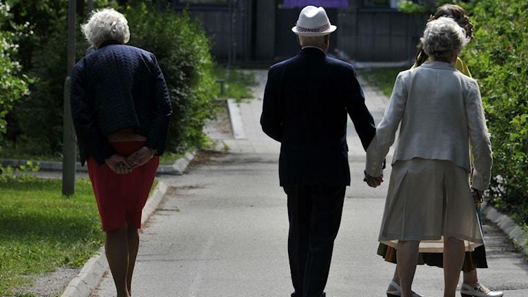 Tre äldre personer är ute och går i sommarkvällen.