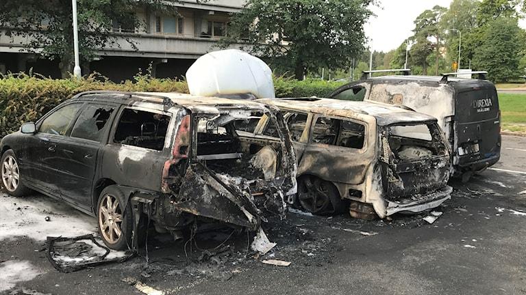 Två helt utbrunna bilar på en parkering i Björkekärr-