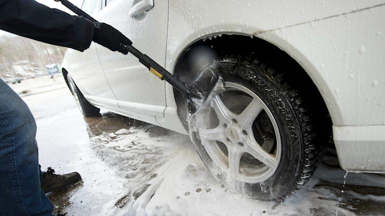 En man sköljer av en bils däck i en tvätthall