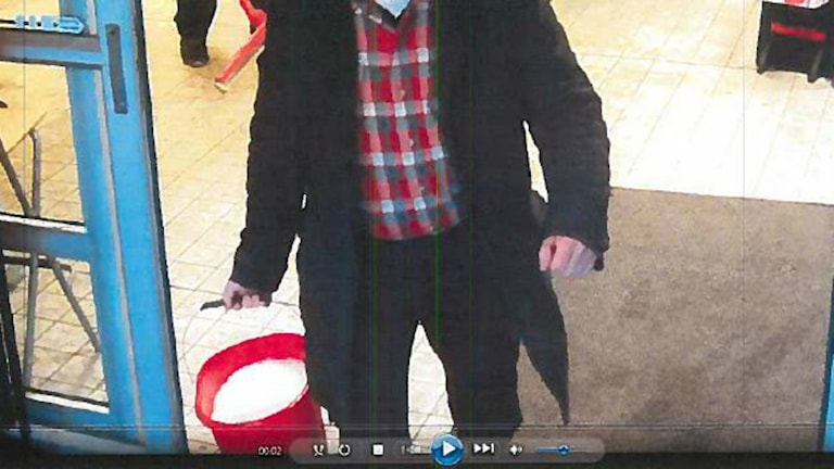 En bild från en övervakningskamera på butikschefen på Stigbergstorget som åtalas för att ha slängt vatten på en tiggare.