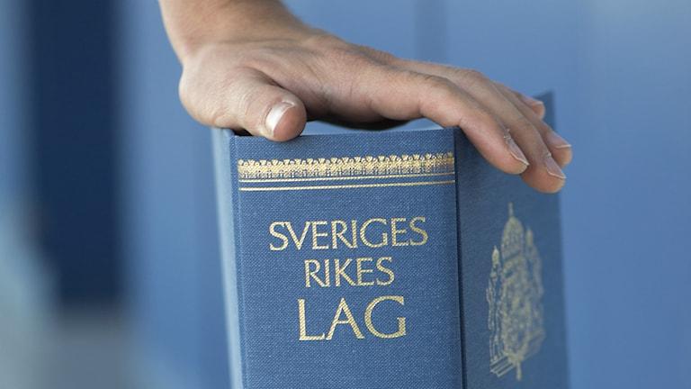 En hand hålls på lagboken, Sveriges rikes lag, anno 2013.