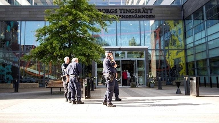 Bild på poliser utanför Göteborgs tingsrätt
