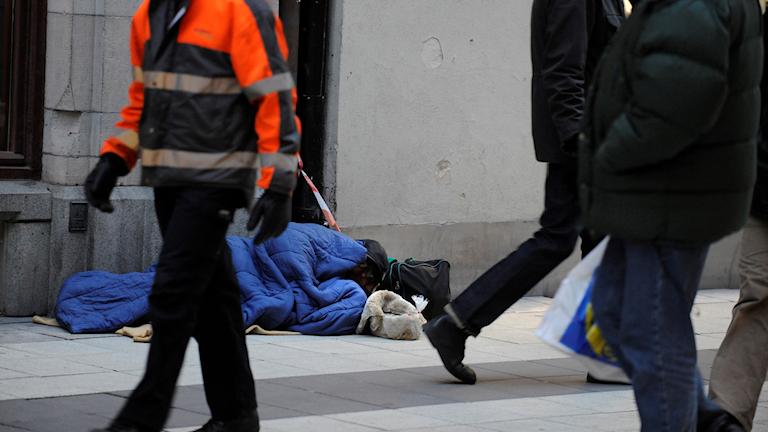 En person ligger i sovsäck på en gata, framför passerar människor förbi.