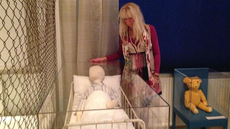 Maya Olsén från föreningen Samhällets Styvbarn vid en barnsäng på Göteborgs stadsmuseum. Foto: Erica Hedin