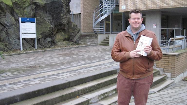 Dietisten Frode Slinde med ett exemplar av Nordiska rådets näringsrekommendationer för oss i Norden. Foto: Epp Anderson/Sveriges Radio