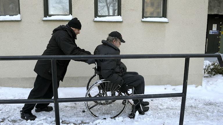 Man skjuter på en rullstol med en man i