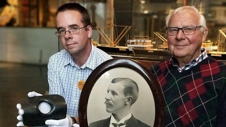 Museiintendent Karl Hellervik håller i genomskjuten däcksplåt. Håkan Rosell håller i bild av sin farfar Gotthilf Rosell.