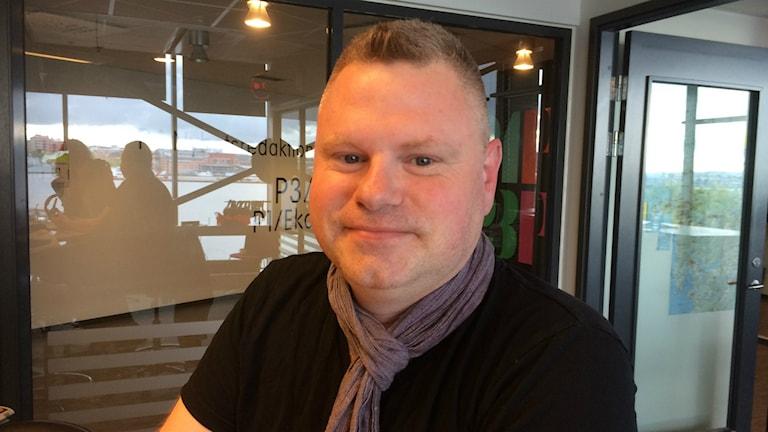 Joakim Berlin från Positiva Gruppen Väst är i studion. Tittar in i kameran med svart tröja och en plommonfärgad sjal. Foto: Ylva Nilsson/SR