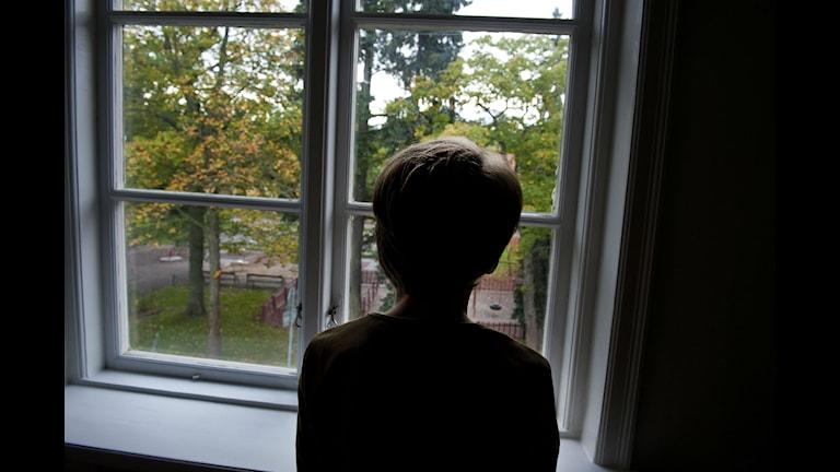 Siluett av ett barn som tittar ut genom ett fönster