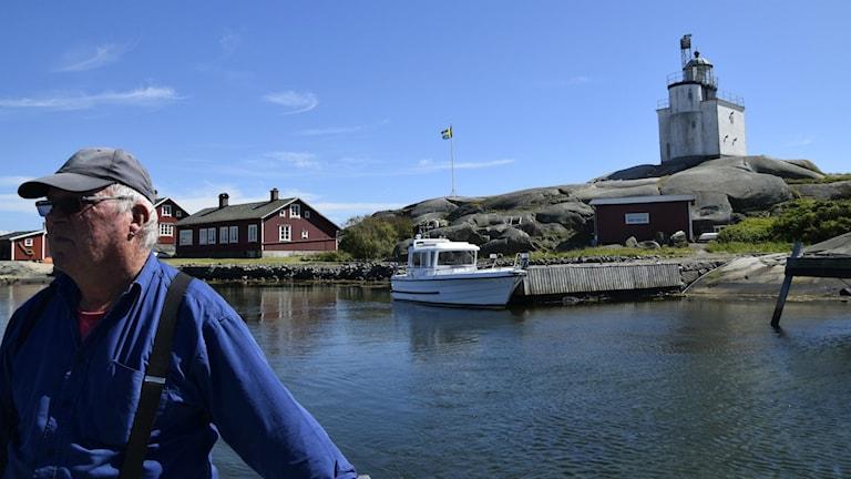 Göran Westerberg till vänster i bild med vatten bakom sig. Fyren synd över viken uppe till höger.  Foto: Mats Carlsson Lenart/Privat.