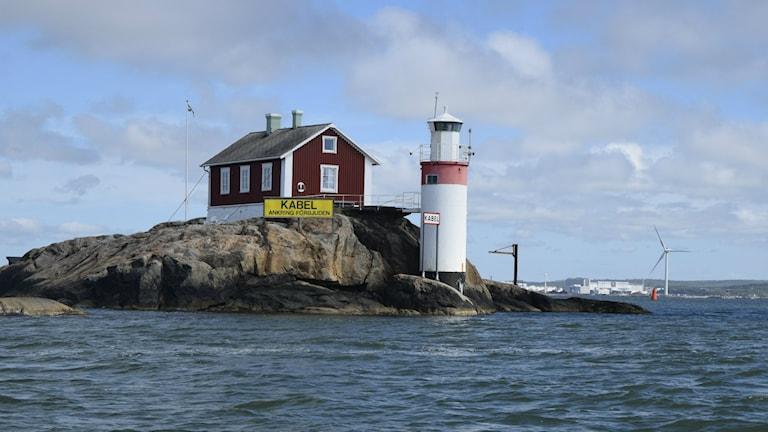 Gäveskärs fyr precis vid vattnet, en liten röd stuga på en klippa bredvid. Vatten i förgrunden.  Foto: Mats Carlsson Lenart/SR.
