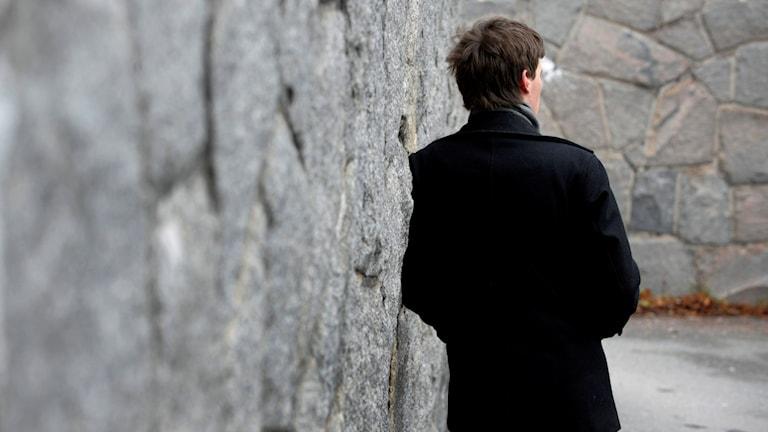 Foto taget bakifrån på en man som står vid en mur. Foto: Jan-Erik Henriksson/TT (ARKIV)