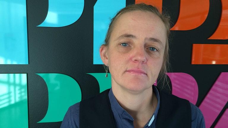 Närbild på vit kvinna med något sorgsen uppsyn. I bakgrunden en vägg där det står P1, P2, P3 och P4. Foto: Ylva Nilsson/SR.