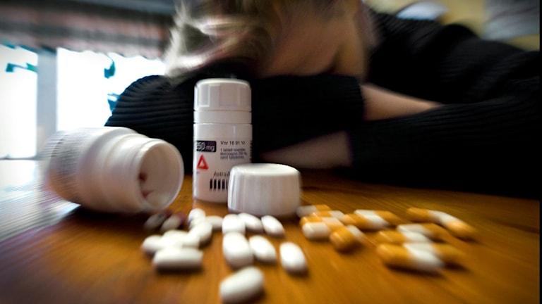 En person i bakgrunden som ligger med armarna i kors på ett bord. Pillerburkar med massa tabletter utspillda framför. Foto: CLAUDIO BRESCIANI/TT