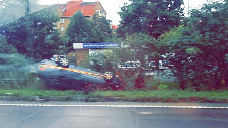 Bil som hamnat på taket efter att ha voltat. Foto: Dino Mesic