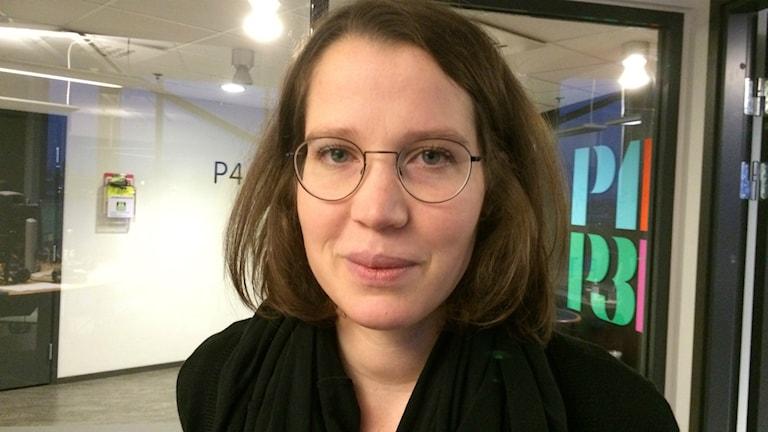 Bild på vit kvinna, brunt hår, runda glasögonon och svar tröja. Foto: Ylva Nilsson/SR.