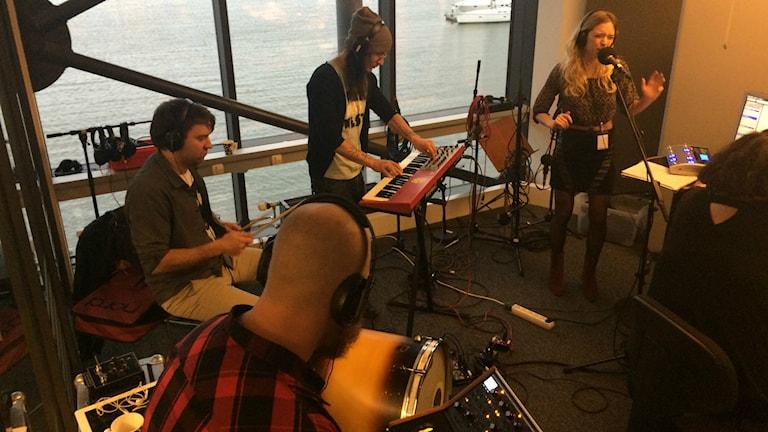 Bild tagen uppifrån på ett band i studion som sitter vid diverse instrument. Synth, trummor och en som sjunger. Foto: Peo Wenander/SR.